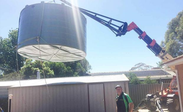 Lifting a 24000 litre rain water tank over a garage roof